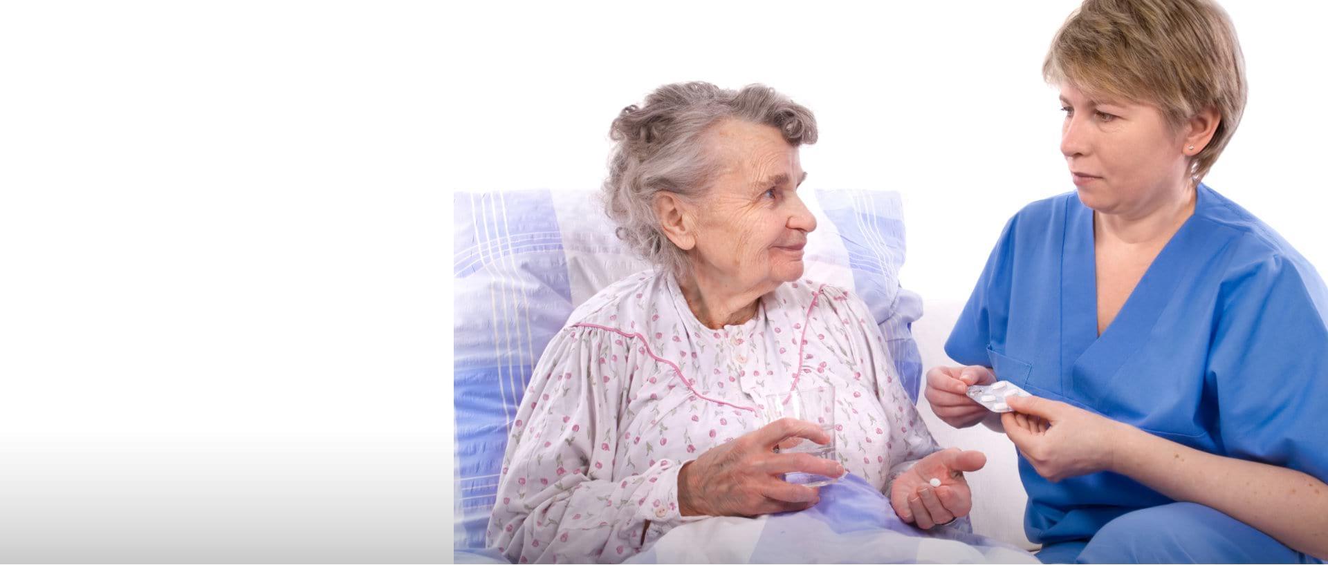 caregiver giving medicines to senior woman