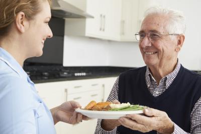 happy nurse giving food to elderly man
